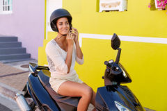 Woman on scooter. Woman sitting on her scooter, strapping her helmet Royalty Free Stock Photography