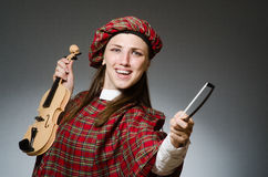 The woman in scottish clothing in musical concept Stock Image