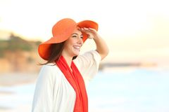 Woman scouting in the beach with hand on forehead. Happy woman scouting in the beach with hand on forehead with the sea in the background Stock Image