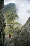 Woman scrambling in the mountains Stock Photo