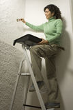Woman Scrapes Wall While Holding Paint Tray Royalty Free Stock Images