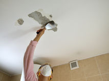 Woman Scraping a Ceiling Stock Photo