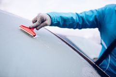 Woman scraping frozen front car windshield Royalty Free Stock Image