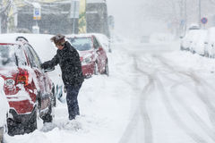 Woman scraping frozen snow from her car windows Royalty Free Stock Photos