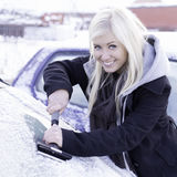 Woman scraping ice. Happy woman scraping ice from car royalty free stock photos