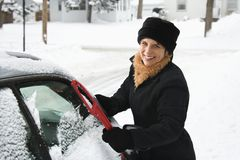 Woman scraping ice off car. Royalty Free Stock Photography