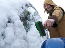 Woman scraping ice off car window Stock Photos