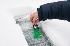 Woman scraping ice and snow Stock Photo