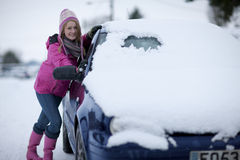 Woman scraping winter snow from car Royalty Free Stock Photo