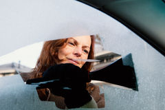 Woman scrapping side window of her car. Royalty Free Stock Image