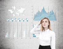 Woman scratches head, four graphs on concrete Stock Photography
