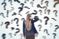 Woman scratching head and looking at blurred question marks Royalty Free Stock Photos