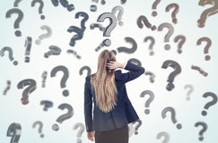 Woman scratching head and looking at question marks Royalty Free Stock Photography