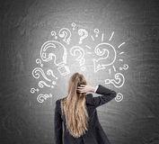 Woman scratching head and question marks on blackboard Royalty Free Stock Photo