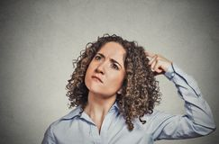 Woman scratching head thinking daydreaming about something wondering. Closeup portrait young woman scratching head, thinking daydreaming about something Stock Photography