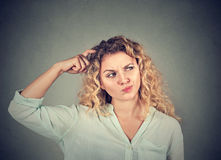 Woman scratching head thinking about something looking up Royalty Free Stock Photo