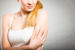 Woman scratching her itchy arm with allergy rash. Health problem, skin diseases. Young woman scratching her itchy arm with allergy rash Royalty Free Stock Images