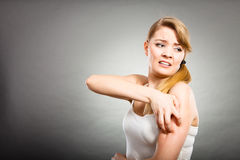 Woman scratching her itchy arm with allergy rash Royalty Free Stock Photo