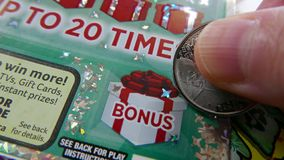 Woman scratching lottery ticket on bonus section. stock photography