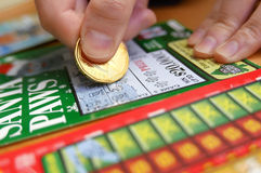 Woman scratching lottery ticket Stock Photography