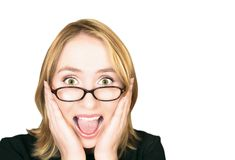 Woman screaming. Young blond woman with large green eyes in glasses holding her head in her hands and screaming with joy Royalty Free Stock Photo