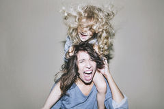 Woman is screaming and arguing with a child on his shoulders cli. Nging to her hair Royalty Free Stock Images