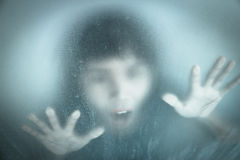 Woman screaming behind stained or dirty window glass Stock Photo