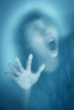 Woman screaming behind stained or dirty window glass Royalty Free Stock Photo