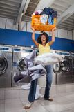 Woman Screaming While Carrying Overloaded Laundry. Young woman screaming while carrying overloaded laundry basket at laundromat Stock Photo