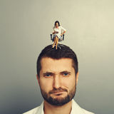 Woman screaming at discontented man. Angry small women screaming at discontented men over grey background stock photo