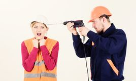 Woman with screaming face in helmet, hard hat. Husband annoying. His wife. Man with drill tool drills head of woman, white background. Builder, repairman makes stock photography