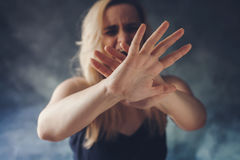 Woman screaming in fear, defending herself with hands. In front of her face royalty free stock images