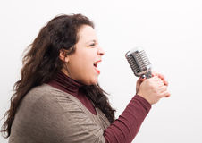 Woman screaming and grabbing a microphone Stock Images