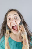 Woman screaming with ham leg in her face. Royalty Free Stock Image