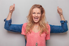 Woman screaming while her lover is standing behind her. Young blonde women screaming while her lover is standing behind her showing the thumbs up gesture with Stock Photo