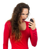 Woman screaming at her phone. A very angry, annoyed and frustrated woman screaming at her phone in rage. Isolated on white Royalty Free Stock Images