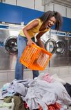 Woman Screaming While Holding Basket With Clothes. Portrait of young woman screaming while holding empty basket with clothes on floor at laundromat Royalty Free Stock Photo