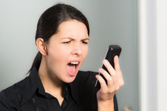 Woman screaming while looking at her mobile phone. Portrait of a brunette Caucasian young woman screaming while looking at her mobile phone, symbol of stress and Royalty Free Stock Photo