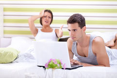 Woman screaming at man while he works on laptop. Problems in bed, women screaming at men while he works on laptop Royalty Free Stock Image