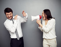 Woman screaming in megaphone at the man Stock Photos