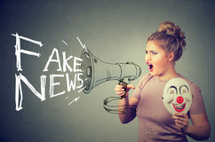 Woman screaming in a megaphone spreading fake news. Woman screaming in a megaphone spreading fake social media news Stock Image