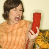 Woman screaming at phone. Pretty Caucasian mid-adult woman screaming at red telephone receiver Stock Photos