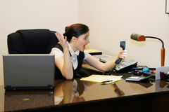 Woman Screaming at Phone. Businesswoman screaming at her phone handset while working at her desk Royalty Free Stock Photo