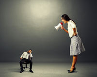 Woman screaming at small lazy man. Angry young women screaming at small lazy man Stock Image