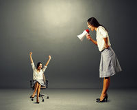 Woman screaming at small woman on the office chair Royalty Free Stock Images
