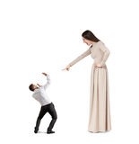 Woman screaming at startled man. Angry women in long dress screaming at small startled man. isolated on white background Royalty Free Stock Photography