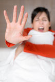 Woman screaming stop abuse. Woman screaming and showing hand for stopping abuses, noises or problems. Fear concept with scared brunette model in bed Stock Images