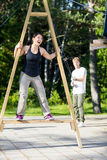 Woman Screaming On Structure While Friend Pulling Ropes On Patio. Full length of happy mature women screaming on wooden structure while friend pulling ropes Royalty Free Stock Photos