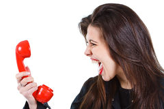 Woman screaming into telephone. Portrait of a beautiful young woman with long brown hair, screaming into a red retro telephone receiver - isolated on white Stock Photo