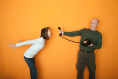 Woman Screaming On Telephone Conversation. Middle-aged man holds telephone while woman screams at it Stock Images